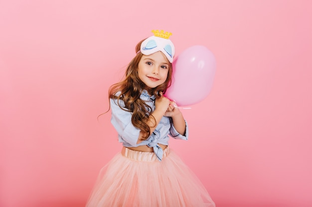 Pretty sweet little girl with long brunette hair hugging balloon, looking to camera isolated on pink background. beautiful joyful child having fun, celebrating birthday party, expressing positivity