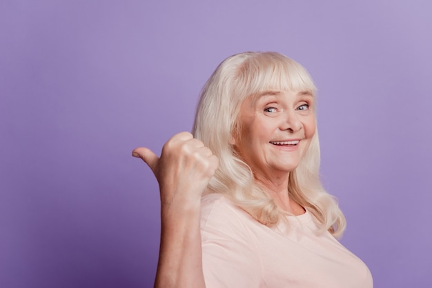 꽤 달콤한 성숙한 여자 가리키는 손가락 빈 공간 고립 된 보라색 배경