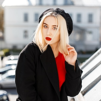明るい晴れた秋の日に街でポーズをとって赤いシャツを着た黒いトレンディなコートを着たファッショナブルなベレー帽の赤い唇を持つかなり甘い若い女性