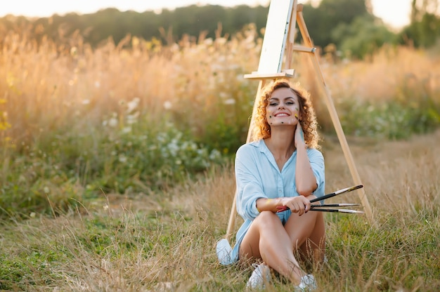 Pretty talented female painter painting on easel, making colorful sketches, creating marine landscape. beautiful female artist painting with watercolor paints. creativity and imagination concept.