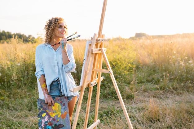 イーゼルに絵を描いたり、カラフルなスケッチを作ったり、海の風景を作ったりする、かなり才能のある女性画家。水彩絵の具で絵を描く美しい女性アーティスト。創造性と想像力の概念。