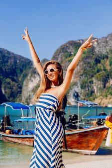 Ragazza del viaggiatore con zaino e sacco a pelo abbastanza tan che posa all'isola tropicale calda di phi phi, vista stupefacente sulle barche e sulle montagne locali