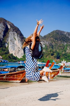 Pretty tan backpacker girl posing at hot tropical phi phi island, amazing view on local boats and mountains.