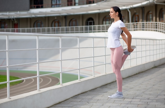 Pretty tanned athletic girl wearing sport apparel doing stretching workout at the stadium. space for text