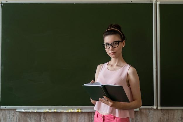 예쁜 선생님은 빈 학교 칠판 근처에서 새 수업을 설명하고 텍스트를 위한 공간을 복사합니다