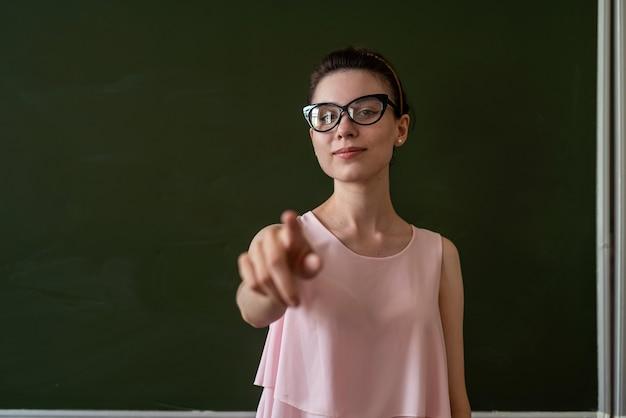 きれいな先生が空の学校の黒板の近くで新しいレッスンを説明し、テキスト用のスペースをコピーします