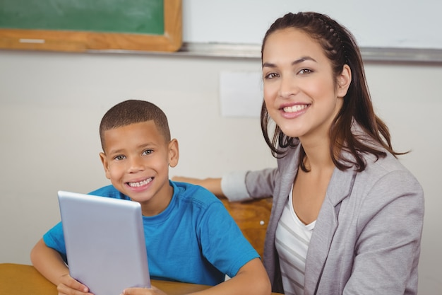 Pretty teacher and pupil with tablet at his desk