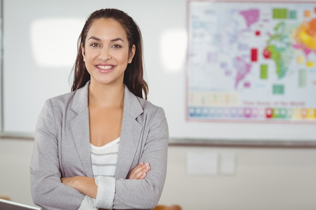 Pretty teacher with arms crossed in a classroom