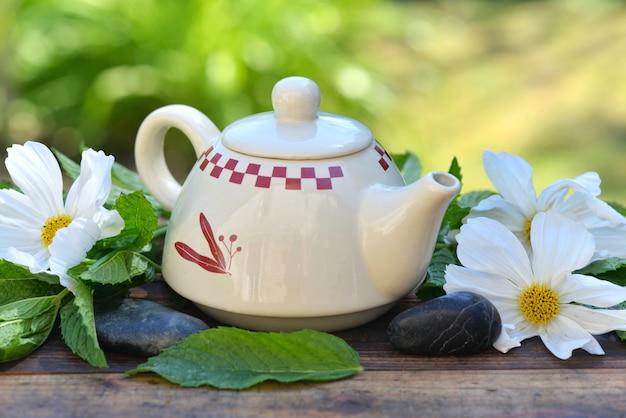 Милый чайник среди листьев свежей мяты и белых цветков на деревянном столе