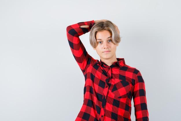 Ragazzo abbastanza teenager in camicia a quadri con la mano dietro la testa e guardando intelligente, vista frontale.