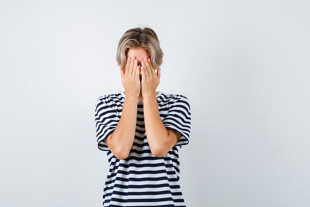 縞模様のtシャツで顔を手で覆い、怖がっているかわいい十代の少年。正面図。