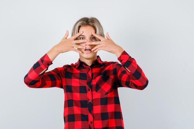 체크 셔츠를 입은 예쁜 10대 소년이 손가락을 통해 보고 겁에 질려 앞모습을 보고 있습니다.