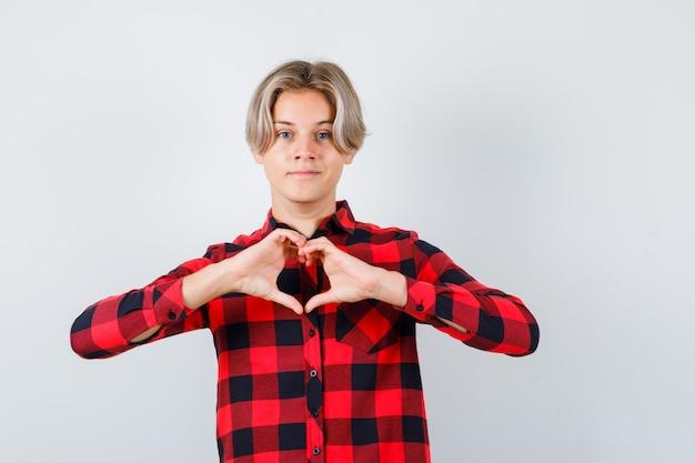 Симпатичный мальчик-подросток в клетчатой рубашке показывает жест сердца и выглядит веселым, вид спереди.