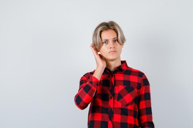 체크 셔츠를 입은 예쁜 10대 소년이 손으로 귀 근처에 있고 혼란스러워 보이는 전면 모습입니다.