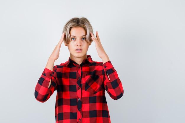 체크 셔츠를 입은 예쁜 십 대 소년이 머리에 손을 얹고 고민하고 있는 전면 모습입니다.