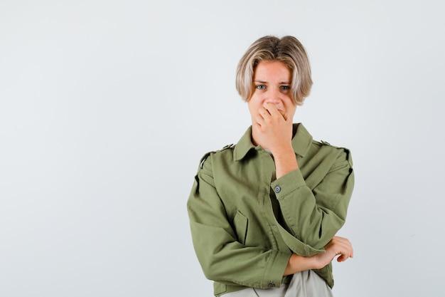 緑のジャケットを着たかわいい10代の少年は、感情的に爪を噛み、不安そうに見える、正面図。