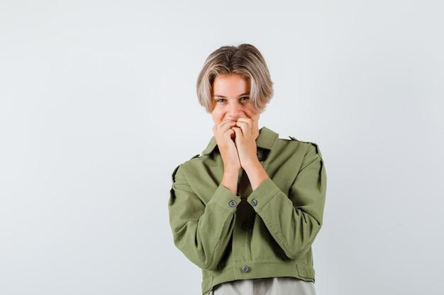 緑のジャケットを着たかわいい十代の少年が口に手を保ち、嬉しそうに見える、正面図。