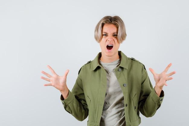 緑のジャケットを着たかわいい10代の少年が、叫びながら攻撃的に見える猫を模倣した爪を見せています
