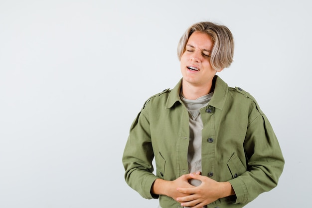 Симпатичный мальчик-подросток в зеленой куртке страдает от боли в животе и выглядит обеспокоенным, вид спереди.