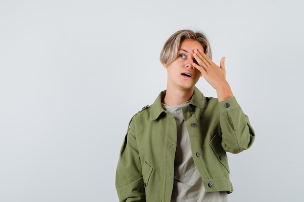 Ragazzo abbastanza teenager che tiene la mano sull'occhio, alzando lo sguardo in giacca verde e guardando meravigliato, vista frontale.