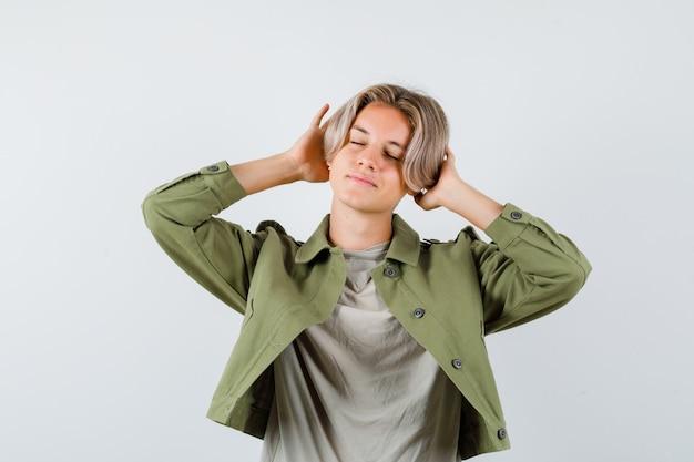 예쁜 10대 소년이 귀 뒤에 손을 얹고 녹색 재킷을 입고 눈을 감고 기뻐하며 정면을 바라보고 있습니다.