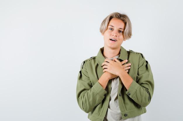 Ragazzo abbastanza teenager che tiene le mani sul petto in giacca verde e sembra grato. vista frontale.