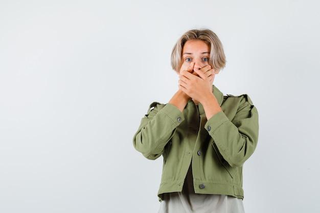 예쁜 십 대 소년 녹색 재킷에 입에 손을 유지 하 고 무서 워 찾고, 전면 보기.