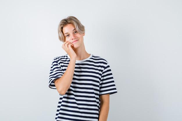 Ragazzo abbastanza teenager che si appoggia la guancia a portata di mano in maglietta a righe e sembra allegro, vista frontale.