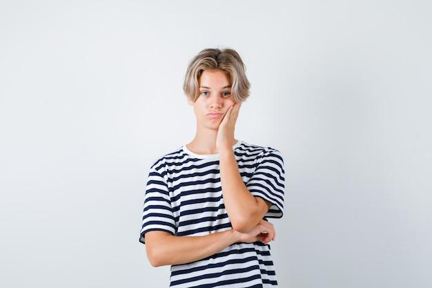 縞模様のtシャツを着て頬を傾けて退屈そうに見えるかわいい10代の少年。正面図。