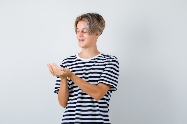 Симпатичный мальчик-подросток, глядя на его сложенные чашкой руки в полосатой футболке и выглядел веселым, вид спереди.