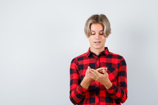 Симпатичный мальчик-подросток смотрит на его ладонь в клетчатой рубашке и выглядит обнадеживающим, вид спереди.