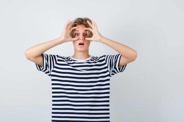 Симпатичный мальчик-подросток смотрит сквозь пальцы в полосатой футболке и выглядит удивленным, вид спереди.