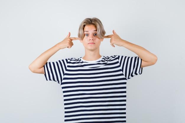 Ragazzo abbastanza teenager che tappa le orecchie con le dita in maglietta a righe e sembra sconcertato, vista frontale.