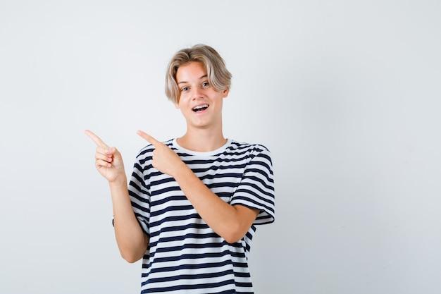 Симпатичный мальчик-подросток, указывая на верхний левый угол в полосатой футболке и выглядел весело, вид спереди.