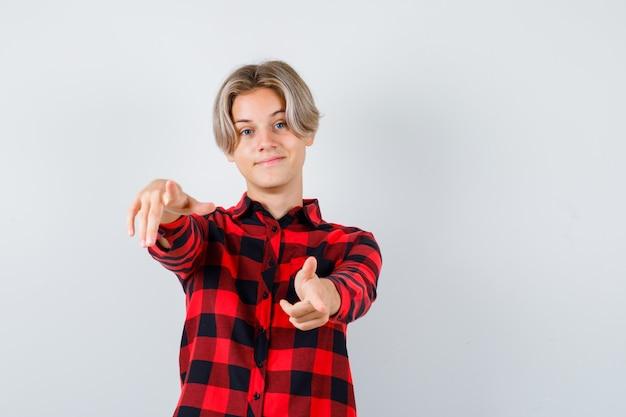 Симпатичный мальчик-подросток, указывая вперед в клетчатой рубашке и уверенно глядя, вид спереди.