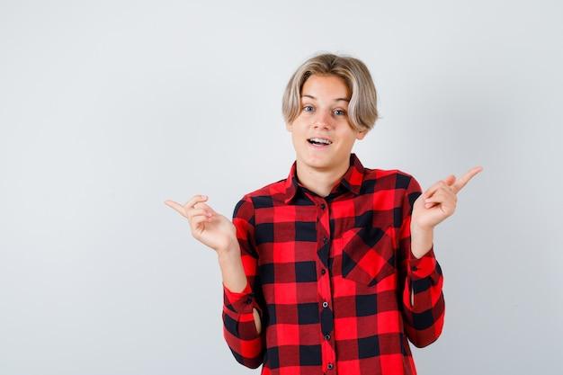 Симпатичный мальчик-подросток, указывающий вправо и влево в клетчатой рубашке и веселый вид. передний план.