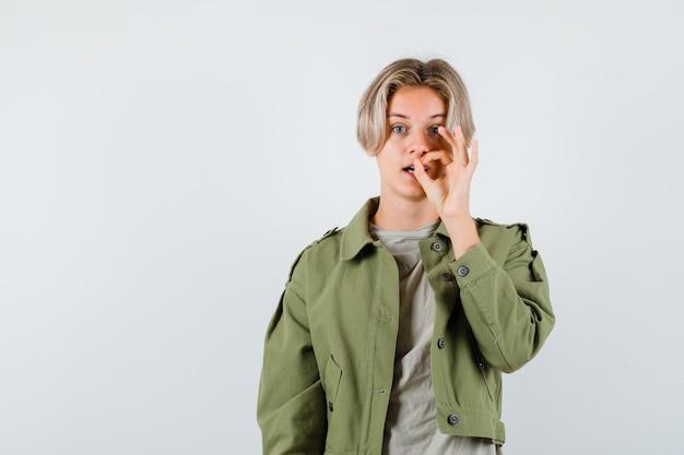 Ragazzo abbastanza teenager che mostra gesto ok in giacca verde e sembra meravigliato
