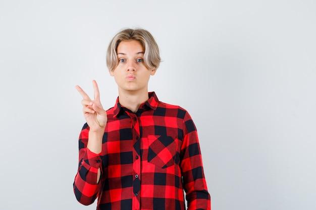 Симпатичный мальчик-подросток показывает жест мира, надувает губы в клетчатой рубашке и выглядит изумленным, вид спереди.