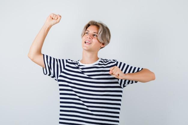 Симпатичный мальчик-подросток показывает жест победителя в полосатой футболке и выглядит счастливым, вид спереди.