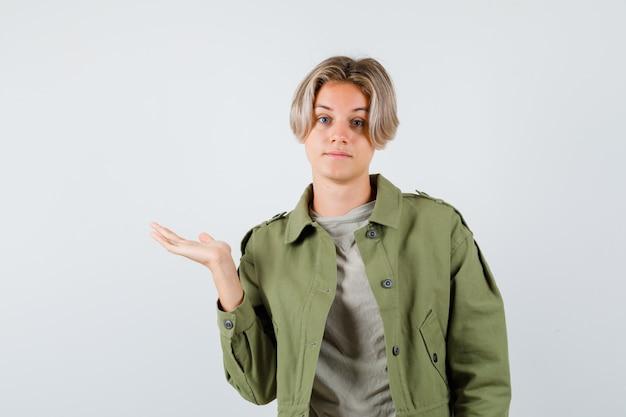 緑のジャケットで手のひらを横に広げて、優柔不断な正面図を見てかわいい十代の少年。