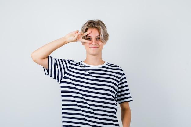 Ragazzo abbastanza teenager in maglietta a strisce che mostra il segno di v vicino all'occhio e che sembra allegro, vista frontale.