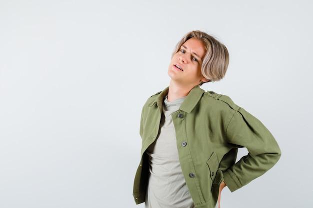 녹색 재킷에 요통으로 고통 받고 지쳐 보이는 예쁜 십 대 소년