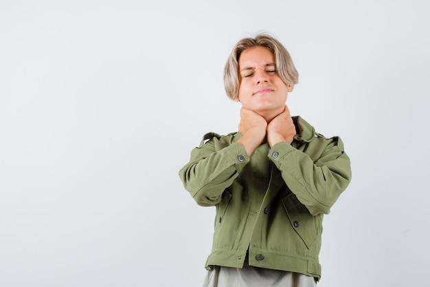 Симпатичный мальчик-подросток страдает от боли в шее в зеленой куртке и выглядит обеспокоенным. передний план.