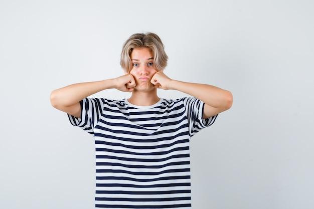 縞模様のtシャツで拳に寄りかかって、欲求不満に見える、正面図で頬をしゃがんでいるかわいい10代の少年。