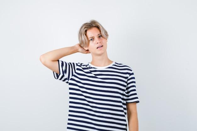 줄무늬 티셔츠를 입고 머리 뒤에 손을 얹고 혼란스러워 보이는 10대 소년.