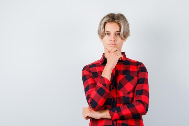 Симпатичный мальчик-подросток с рукой на подбородке в клетчатой рубашке и задумчивый взгляд. передний план.