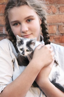 Pretty teen girl is holding small sad  kitten in her arms outdoors. social problem to helping of homeless animals.