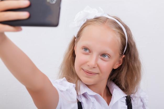 彼女のスマートフォンでselfiesを取るかわいい十代の少女
