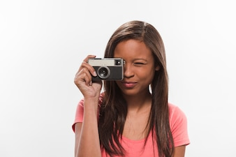 Pretty teenage girl clicking photograph through camera