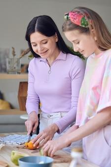 Довольно девочка-подросток режет фрукты во время приготовления завтрака с матерью на кухне